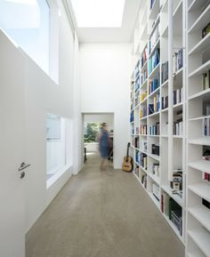 Haus von Arx / Haberstroh Schneider All shelving in hall to bedrooms keeps clutter out of the way from guests to see, making public space more peaceful.