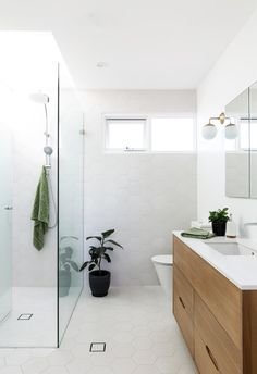 White and bright bathroom with green indoor plants and timber vanity in coastal home on Sydney's northern beaches. Modern Coastal, Mid-century Modern, Timber Vanity, Mid Century Bathroom, Mid Century Armchair, Bathroom Design Inspiration, Indoor Outdoor Living, Mid Century House, Coastal Homes
