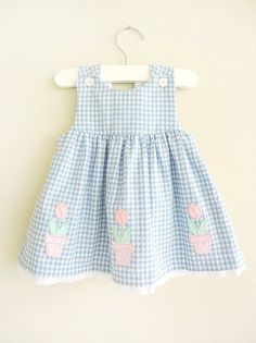 Sweet vintage blue gingham pink flower dress. Embroidered pink flowers in gingham pots, white lace hem, sleeveless shoulders with 2 buttons in front. Size 6-9mo.    Shoulders: 8  Waist: 10  Length: 15    In excellent vintage condition! Visit my entire shop:  http://www.REiNViNTAGEkids.etsy.com    Like my shop for sales & newly listed items:  http://www.facebook.com/pages/REiNViNTAGEkids/156392281074009    Check out my women & mens vintage shop!  http://www.shopREiNViNTAGE.etsy.com