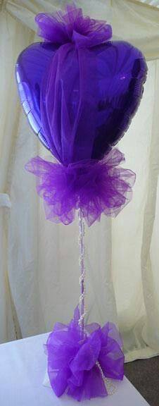 A tulle covered heart shaped foil balloon.  The foil balloon can be in whatever color compliments your theme.  Makes a great centerpiece.