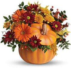Orange gerberas, bronze cushion mums, red daisies, huckleberry and salal are accented with yellow oak leaves and artificial fall berries.