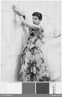 NK efter idé från Dior, 1955. Modell i blommig klänning med rosett och örhängen vid en vägg. Fotograf: Nordin/Nilson