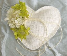 This pillow is an example of what you can do by adding flowers and ribbon to the simple burlap heart pillows...fun...Burlap Ring Pillow Handmade Heart White $14