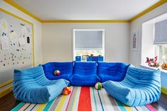 Contemporary playroom features light gray paint on walls finished with yellow crown moldings and yellow base boards lined with an extra-large magnetic board framed with yellow molding.