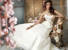 The white dress relates the photo to weddings, which are definitely romantic. She is also sitting in an ornate set with pink flowers artfully placed.