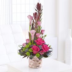 This Calla lily arrangement looks magnificent and elegant, as its accompanied by lime green chrysanthemums and cerise roses.