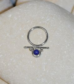 ⋙ Sterling Silver lapis lazuli septum ring. ⋙ This listing is for one earring. ⋙ Available gauges for the ring: 20g; 18g; 16g. ⋙ Please note: the less gauge number, the thicker ring is. ⋙ Available interior (inner) diameters: 8mm; 9mm; 10mm; 11mm; 12mm. ⋙ Available gemstones: white opal; kiwi green opal; ruby; lapis lazuli; swiss blue topaz; turquoise; white pearl; amethyst; black onyx; emerald; garnet; light blue opal; black-red opal; blue sapphire; clear white topaz ⋙ Measurements: ⋙ The…
