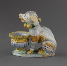 Musée d'Ecouen- Salière en forme de chien. ECL7580. Assis devant une petite vasque godronnée, le chien porte un collier à 6 grelots. Profil gauche. 17°s. DERUTA (origine) Faïence Ht: 0.14 Largeur: 0.137 Profondeur: 0.065 m.