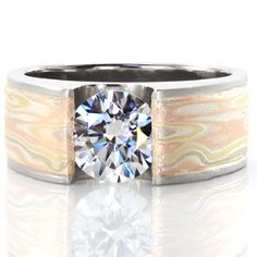 Stunning, unique, custom diamond engagement ring design. Modern design done in a 4-metal mokume gane technique. This piece features a wide, flat band leading up to a half bezel setting around the diamond. Solstice - Autumn Wind from Knox Jewelers #mokumegane #solitaire