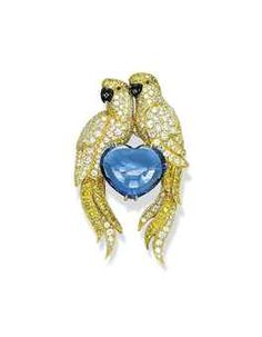 A DIAMOND, COLOURED DIAMOND AND SAPPHIRE BROOCH, BY CARTIER Designed as two lovebirds, each with pavé-set diamond and yellow diamond body, head and tail, ruby eyes and onyx beak, perched on a heart-shaped sapphire, 5.3 cm