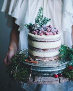 Unfrosted cake, topped with evergreen branches and sugared cranberries—perfect for a small winter wedding #InStyle