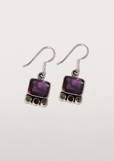 Three varieties of semi-precious stone are set in these sterling silver earrings. Find an amethyst centrepiece offset by peridot and garnet accents. A harmony of elements!