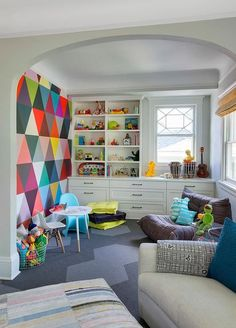 Colorful contemporary playroom features a modern play table seating a blue Panton Junior Chair and molded plastic play chair in front of a graphic geometric print accent wall.
