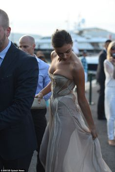 Sheer delight: The daring dress left little to the imagination as Irina rearranged the dress in the sunlight