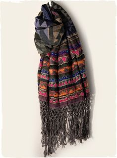 The gorgeous wool (60%) and cotton (40%) shawl is embroidered in bands of vibrant geometrics and finished with long macramé fringe.