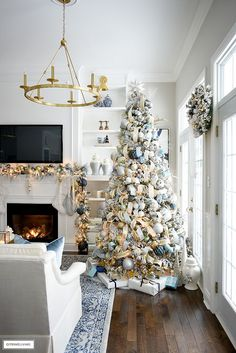 Elegant Christmas Living Room: Soft Blue + Gold - CITRINELIVING Christmas living room decorating ideas, flocked tree and garland with blue and gold decor.