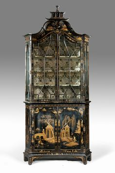 A striking black and gilt Chinoiserie bookcase.  The glazed upper section of this bookcase has astragal glazing bars and is surmounted by a double scroll pediment and a pagoda. The base comprises two cupboard doors. Decorated overall with oriental landscapes in gilt on black. 	 Circa 1910