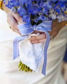 Blue delphinium blooms are finished off with blue ribbon and a vintage handkerchief in this sweet arrangement.
