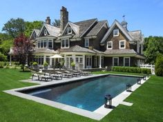 Love this dark shingled white trimmed house and love the slate stone around the pool area!