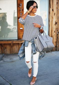 Julie Sarinana of Sincerely Jules wearing a striped top, denim jacket tied around the waist, white ripped jeans, and flats.