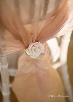 Una silla de chiavari con una tela de organza en rosa oscuro y oro atado con una rosa blanca. Fotografía: Niki Kirk.