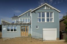 Photo of a house clad with Marley Cedral concrete fibre weatherboard. glass gable panels at differing heights
