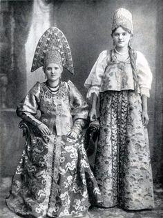 two Russian women in traditional costumes. Sitting lady wears sarafan (dress), shugay (short jacket), one-horned kokoshnik. Standing lady wears sarafan, dushegreya (bodice) and kind of kika (headdress) Army Costume, Folk Costume, Costumes, Russian Folk, Russian Art, Russian Style, Folklore Russe, Costume Russe, Style Russe