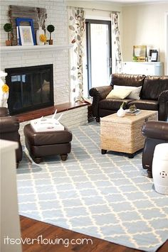 Family Room with blue rug and yellow accents. Brown couches and rattan coffee table. Details at ItsOverflowing.com