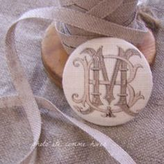 """White linen button """"monograms"""" I can imagine this on a chair back."""