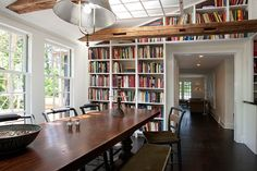 Fabulous farmhouse style dining room with built-in bookshelves in the background