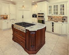 White kitchen cabinets with cherry island. See more in our kitchen cabinet gallery.