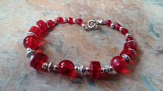 A stunning red glass with silver wheel bead and bracelet hand made to make a loved one smile. can be bought alone or as part of a set with a pair of earrings . Items can be personalised for a loved one Thank you for your time. Handmade Beads, Handmade Gifts, Selling On Pinterest, Red Glass, Rose Quartz, Beaded Bracelets, Bronze, Pearls, Crystals
