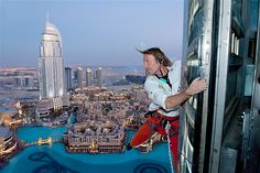 "Alain Robert, known as the French ""Spiderman"", looks across the cityscape as he climbs the Burj Khalifa in Dubai, United Arab Emirates. Unlike many of Roberts recent climbs, the ascent of the 2,717 foot tower was made using rope and harness as security precautions.(© GETTY IMAGES/Emmanuel Aguirre)"