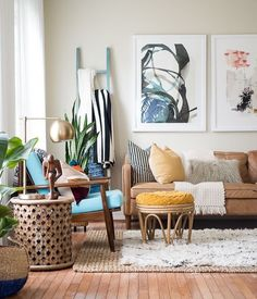 living room | modern | mid century | brown leather sofa | bohemian | eclectic | artwork | plants | yellow | blue | layered rugs