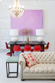 mur de brique blanche décoré d'un tableau rose dans la salle à manger aménagée avec chaises rouges et lampes blanches