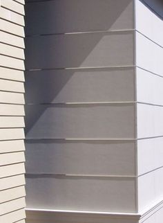 Exterior siding is a collage of fiber cement panels separated by aluminum reveals, and fiber cement clapboards with mitered corners.