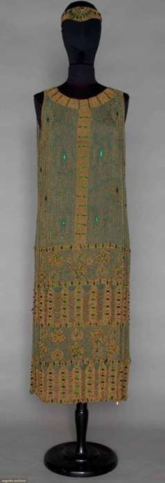 auctionguide: Green and Gold Beaded Dress, c. 1921, Sage green chiffon completely covered in gold beads & green jewels, deep hem w/ 3 dimensional flowers & 2 deep bands of scalloped gold beads