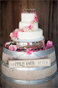 Since the reception is at a vineyard, I love that this cake is displayed on a wine barrel with fresh flowers around the cake. The Happily Ever After sign is cute too :)