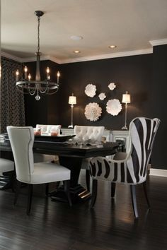 Glamorous white and black dining room with black walls paint color, Candice Olson Light Aristocrat Chandelier, Global Views Carnation Wall Flower Decorative Accent in Pearl White, Global Views Carnation Platter/Bowl Decorative Accent in Pearl White, white mirrored buffet, glossy black dining table, white nailhead trim side chairs and zebra captain dining chairs.