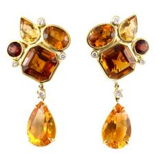 Playful and sophisticated amber colored earrings. These earrings are part of a collection inspired by the whimsical shapes and colors in a kaleidoscope. The open 18kt gold bezel settings in these earrings allow the stones' clarity and color to shine through. The stones include citrine, garnet and yellow beryl. This pair has removable citirine drops that turn these earrings into evening wear show stoppers. Designed and made in-house by Julius Cohen New York. Contemporary