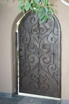 Solid metal gate with curled ironwork detail. This reminds me of many Mexican and Spanish homes. You can't see anything from the street except the wall and the gate, and if the wall isn't too high, the top of the house.