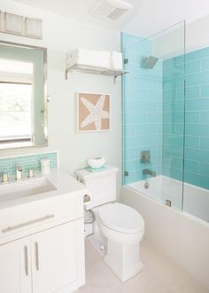 Beach themed bathroom features a drop-in shower clad with turquoise glass tiles lined with a square shower head.