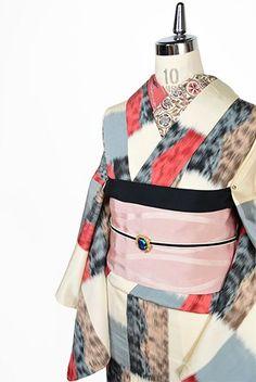 アイボリーに、黒とグレーのモノクロームを基調にピンクベージュとローズピンクをスイートなアクセントにして、大胆な変わり市松が織りだされたアンティークの御召単着物です。