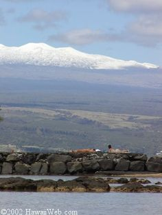 Snow covered Mauna Kea; Onekahakaha Beach in forefront.