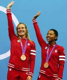 Canada's Jennifer Abel and Emilie Heymans wave after receiving their bronze medals at the women's synchronised 3m springboard victory ceremony during the London 2012 Olympic Games at the Aquatics Centre