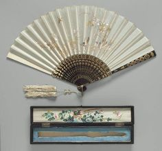 Folding fan Chinese for export, Qing Dynasty, Late 19th to early 20th century China Dimensions Overall: 31.5cm (12 3/8in.) Other (open maximum): 53.5cm (21 1/16in.) Medium or Technique Silk plain weave with silk embroidery; lacquer; painted silk; brass. MFA museum, Boston.