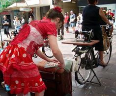 """Sewing as street art:  Sewists offer to do clothiing """"embelishments"""", but you have to provide the power to the machine by pedaling the bike!"""