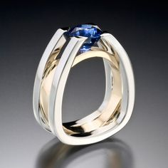 Forte ring shows strength and structure. This architecturally inspired ring suspends a dazzling blue sapphire in white gold with yellow gold accent. Call us at (949) 715-0953 to purchase or click for additional information.