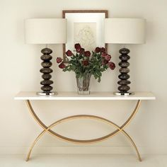 Porta Romana - Large fishtail console table with faux limestone top - bronzed flanked by slender table lamps