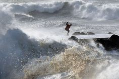 Anglet, France:   A man tries to keep his balance as waves hit the seawall at the beach on Jan. 13.